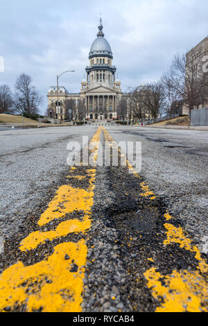 Yellow lines and pot holes on the road leading up to the state capitol building in Springfield, Illinois. - Stock Photo