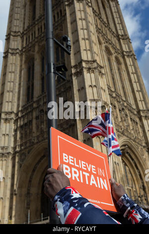 A Brexiteer protestor holds a Believe in Britain placard beneath parliament during a protest on College Greeen in Westminster, the morning after another of Prime Minister Theresa May's Brexit deal votes failed again in Parliament, on 13th March 2019, in London, England. - Stock Photo