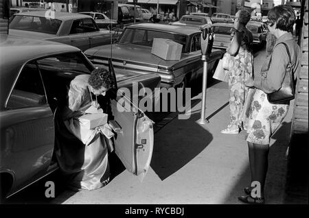 Reno Nevada USA US 1960s, Ladies putting money in parking meter before going to the Casino wearing ball gown. 60s USA  HOMER SYKES - Stock Photo