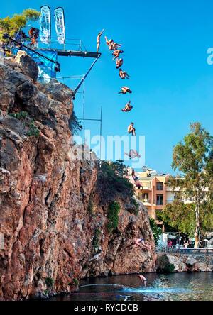 Cliff diving at Voulismeni lake, Agios Nikolaos town, Lasithi prefecture, Crete island, Greece. - Stock Photo