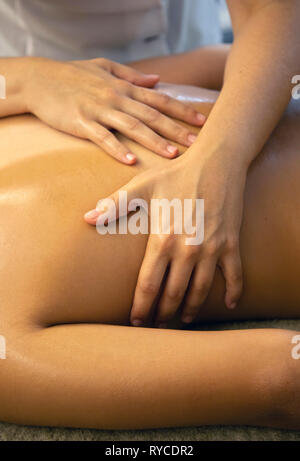 Close up on the hands of a masseuse during a massage treatment in a Spa in Ierapetra town, Crete, Greece. - Stock Photo