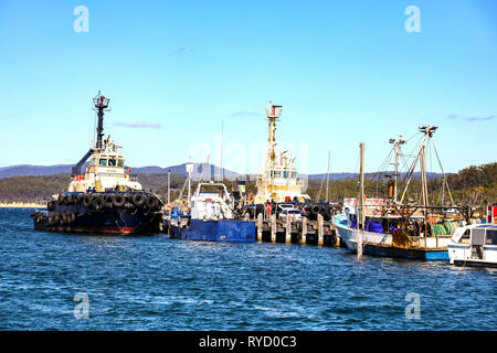 Tug boat and fishing trawlers tied up at wharf in Eden Harbour on Two Fold Bay on the New South Wales southern cost - Stock Photo
