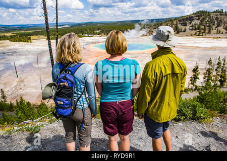 Two women and a man stand on a hill above the Grand Prismatic Hotspring in Yellowstone National Park, Wyoming, USA.