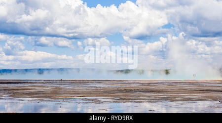Looking across the bacterial matts of the Grand Prismatic spring two tourists on the board walks appear through the steam, Yellowstone National Park,  - Stock Photo