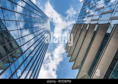 Clouds in a blue sky reflected in the windows of skyscrapers taken from below, a horizontal image of an urban landscape - Stock Photo