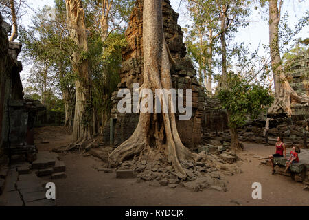 Family visiting ancient Ta Prohm temple in Angkor Archaeological area in Cambodia - Stock Photo