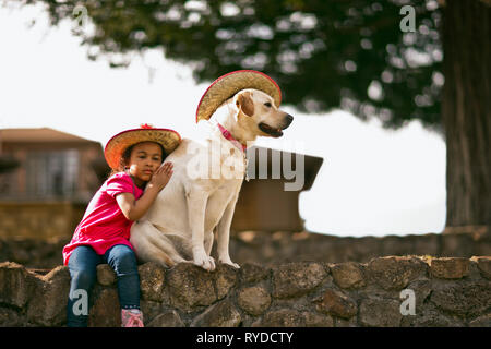 Young girl sitting on a wall with her arm around a dog, both of them wearing cowboy hats. - Stock Photo