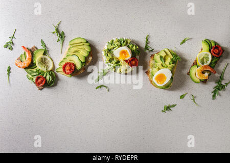 Variety of vegetarian sandwiches with sliced avocado, sun dried tomatoes, egg, shrimps, arugula served over white grey spotted background. Flat lay, s - Stock Photo
