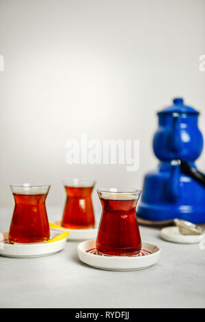 Turkish tea served in three Turkish tea glasses, thin lemon wedges on the side of two. Accompanied by a nostalgic blue teapot set. - Stock Photo
