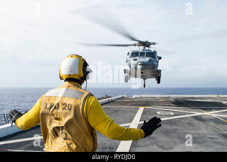 190311-N-DX072-1036 PACIFIC OCEAN (March 11, 2019) – Aviation Boatswain's Mate (Handling) 3rd Class Dion Sanders, from New York, signals to an SH-60S Sea Hawk helicopter assigned to the Island Knights of Helicopter Sea Combat Squadron (HSC) 25 as it lands on the flight deck of the amphibious transport dock ship USS Green Bay (LPD 20) during a training exercise with other U.S. Navy warships. U.S. Navy warships train together to increase the tactical proficiency, lethality, and interoperability of participating units in an Era of Great Power Competition. (U.S. Navy photo by Mass Communication Sp - Stock Photo