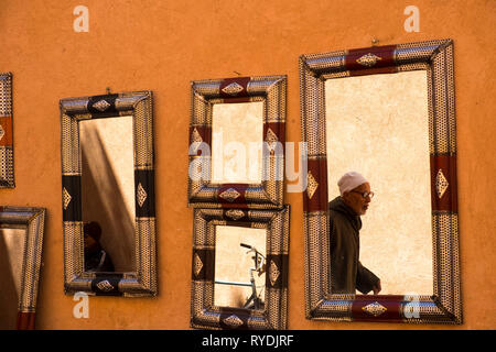Marrakech, Morocco - March 27, 2018: Mirror reflection of man walking in narrow alley in the souq market of the medina - Stock Photo