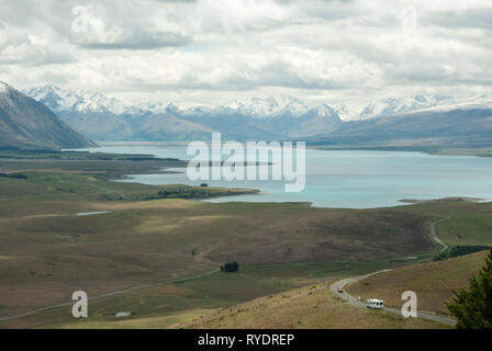 Stunning pale blue Lake Tekapo, NZ; snow capped Southern Alps in the background and meandering road with camping van in foreground. View from Mt John - Stock Photo