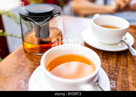 Closeup of two white cups of green black or oolong tea in breakfast outdoor cafe restaurant outside wooden table with orange colorful vibrant vivid co - Stock Photo