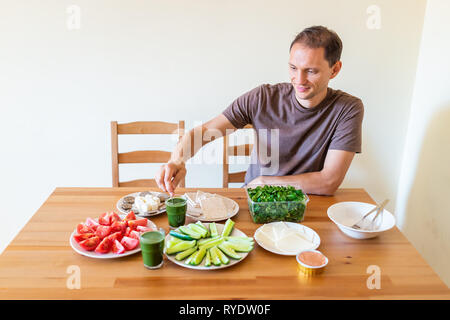 Man sitting on chair by wooden table with setting of healthy vegan vegetarian lunch or dinner green vegetables juice in home - Stock Photo