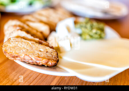 Table with side view closeup of healthy vegan vegetarian lunch or dinner green vegetable cheese slices cubes and smoked baked tempeh with nobody - Stock Photo