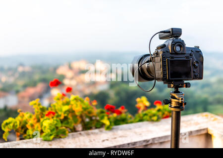 Chiusi Scalo sunset or sunrise of houses buildings in Tuscany, Italy with town cityscape and focus on dslr camera on tripod by flowers garden foregrou - Stock Photo