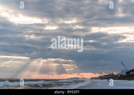 Dramatic magical sunset with sun beams rays in Santa Rosa Beach, Florida with Pensacola coastline coast cityscape skyline in panhandle and ocean gulf  - Stock Photo