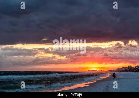 Red orange dramatic sunset and silhouette in Santa Rosa Beach, Florida with hurricane storm coastline coast shore in panhandle with ocean gulf mexico  - Stock Photo