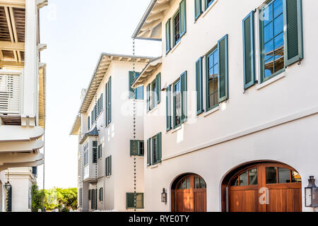 Seaside, USA - April 25, 2018: Wooden houses community parking garage townhomes by beach ocean, nobody on vacation in Florida during sunny day - Stock Photo