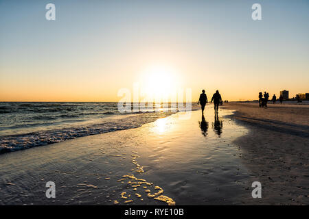 Sarasota, USA Sunset sun in Siesta Key, Florida with coastline ocean gulf of mexico on beach shore and many people couple silhouette walking by waves - Stock Photo