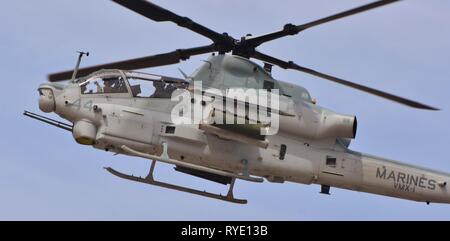 A U.S. Marine Corps AH-1Z Viper attack helicopter flying at MCAS Yuma. This AH-1Z Viper belongs to the VMX-1 squadron. - Stock Photo