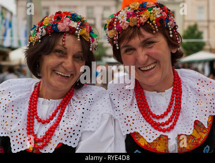 Two Polish women in traditional costumes and beaded headresses are folkloric dancers performing at a festival in Krakow, Poland - Stock Photo