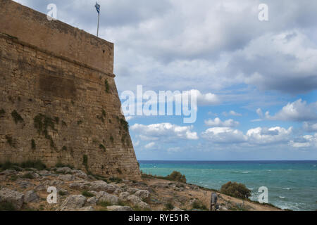 Venetian fortress built on a hill called Paleokastro (Old Castle).  Stone walls and a greek flag. Stone land around, small vegetation. Calm water of t - Stock Photo