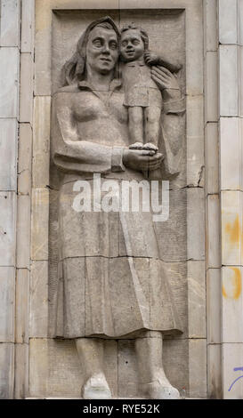 Bas relief of a symbolic depiction of motherhood in the Socialist Realist artistic style near the Constitution Square of Warsaw, Poland. - Stock Photo