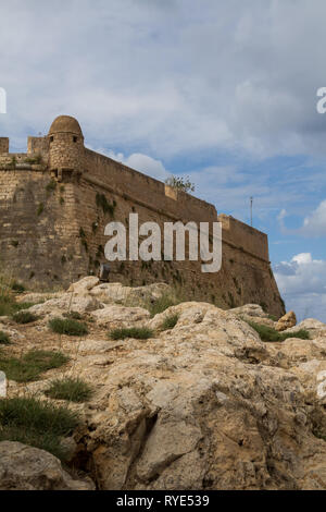 Venetian fortress built on a hill called Paleokastro (Old Castle) built of stones. High walls an a tower. Stone land around with small vegetation. Ret - Stock Photo