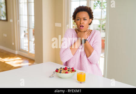 Young african american woman having healthy breakfast in the morning at home shouting and suffocate because painful strangle. Health problem. Asphyxia - Stock Photo