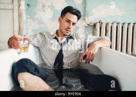 Drunk businessman bankrupt in bathtub, suicide man - Stock Photo