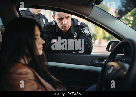 Police officers in uniform check female driver  - Stock Photo