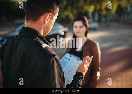 Police officers reads law to female driver - Stock Photo