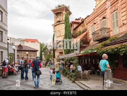 TBILISI, GEORGIA - SEPTEMBER 22, 2018: Crowd of tourists near the Rezo Gabriadze puppet theater with a leaning clock tower - Stock Photo