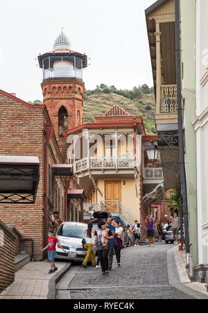 TBILISI, GEORGIA - SEPTEMBER 23, 2018: Many people, tourists and locals, walk on narrow streets of old town Tbilisi near the Juma mosque - Stock Photo