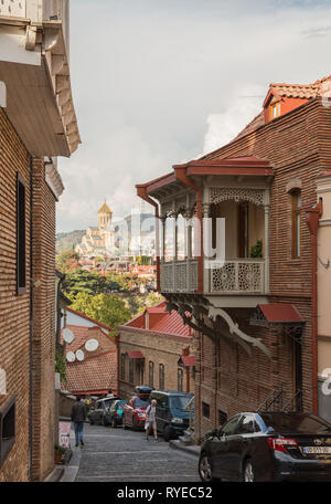 TBILISI, GEORGIA - SEPTEMBER 23, 2018: Scenic view of old city Tbilisi, narrow steep street coming down from hill overlooking the Cathedral of Holy Tr - Stock Photo
