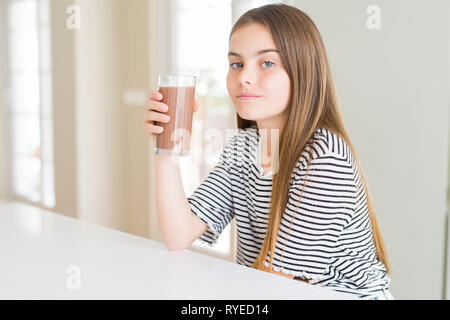 Beautiful young girl kid drinking fresh tasty chocolate milkshake as snack with a confident expression on smart face thinking serious - Stock Photo