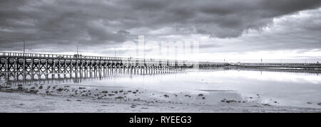 Wooden pier, clouds and stormy sky reflected in calm waters of North Sea - seaside landscape of Northumberland
