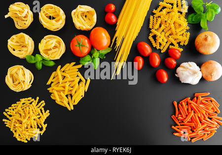 different uncooked italian pasta noodles on dark background with basil leaves, fresh tomatoes and onions - Stock Photo
