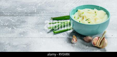 Mashed potatoes with green onions and garlic. On a rustic background. - Stock Photo