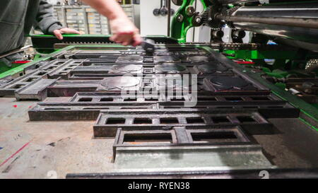 Scrubbing of black ink on the apple metal forms inside the old printing factory - Stock Photo