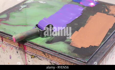 Closer look of the roller with the purple ink on it and a brown color ink on the platform inside the printing station - Stock Photo