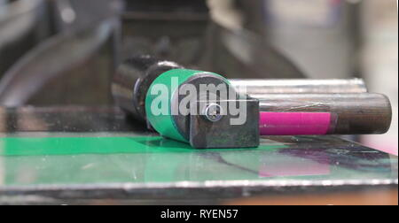 The metal roller with the green ink on it on top of the metal platform inside the old printing shop - Stock Photo