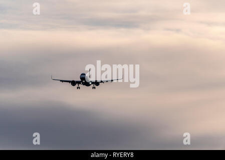 Plane on final approach to land at London Heathrow Airport, London, UK at dawn. Landing airliner jet. Early morning arrival. Space for copy - Stock Photo
