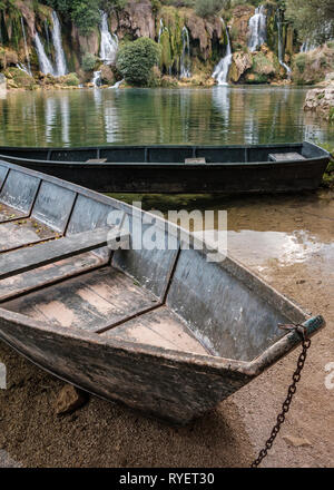 Two wooden boats moored on the shoreline of the Trebizat River with Kravice Falls in the background, Herzegovina, Bosnia and Herzegovina - Stock Photo