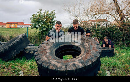 Participants in an obstacle course turning a wheel - Stock Photo