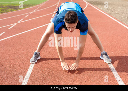 Marathon preparation. Young man on stadium outside standing bending down stretching concentrated - Stock Photo