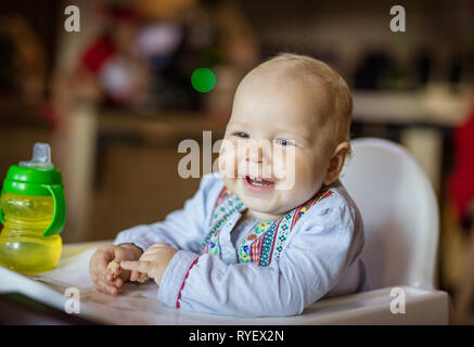 Cute baby girl sitting in high chair, eating piece of bread and smiling
