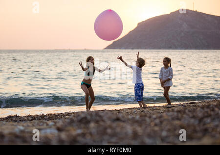 Three young children playing with huge pink balloon on beach at sunset - Stock Photo