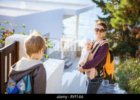 Young woman with baby daughter and preschool son walking down stairs in seaside town. Boy catching behind with mother and sister. - Stock Photo
